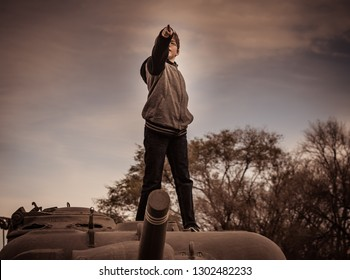 "On a chilly Autumn evening, a boy stands on top of an antique WWII Army tank and points ahead at the sky as if he's saying ""Charge"" in this playful use of childhood imagination and adventure."