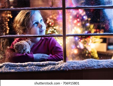 On Christmas night a little girl looks up at the sky out of the window, waiting for Santa Claus. There is frost and snow on the window, the interior of the house is illuminated for Christmas