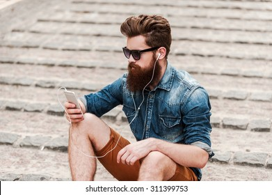 On the city wave. Top view of young bearded man in headphones holding mobile phone while sitting outdoors