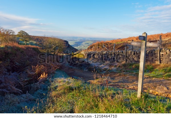 On a clear autumn morning in the Derbyshire Peak District a wooden sign points towards curbar Edge and Baslow Edge.
