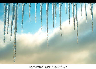 On a clear day, shiny transparent icicles hang. Landscape of winter icicles. Icicles shine in the sun against a blue sky. Snow elements on a winter background.