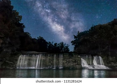 On a clear summer night, the Milky Way Galaxy extends through the night sky over Upper Cataract Falls, a waterfall on Mill Creek in rural Owen County, Indiana.