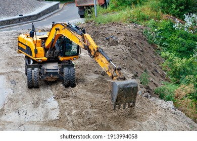 On a cloudy summer day, a construction excavator clears a construction site for the foundation of a future home.