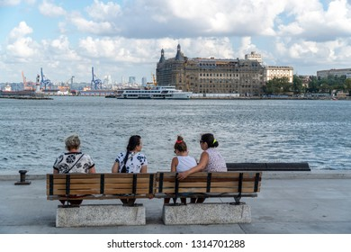 on a clowdy weather, against the sea front and the main harbour, which is next to haydarpasa buılding, the old main train station or main train terminal of istanbul four women are sitting on a wodden