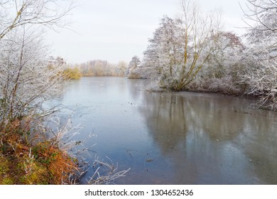 On a cold, misty morning, looking down the length of a shallow, frozen lake fringed with frost covered trees