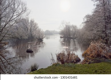 On a cold and misty winters morning frost laden trees and bushes surroung a partially frozen lake