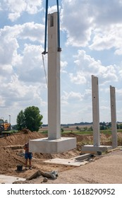 on a construction site, concrete columns for a factory building are placed with the help of a large crane
