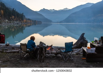 On a cool fall evening  teenage boy sits in front of a fire at his camp site enjoying the view with his dog as the sun dips behind the mountains reflecting them in a still Lillooet Lake.