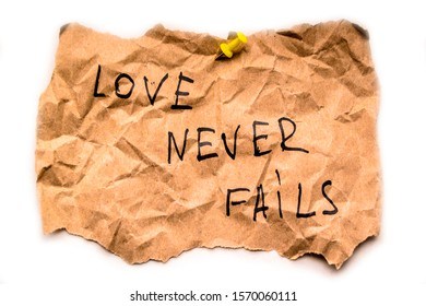 "On crumpled paper, the inscription ""love never fails"""