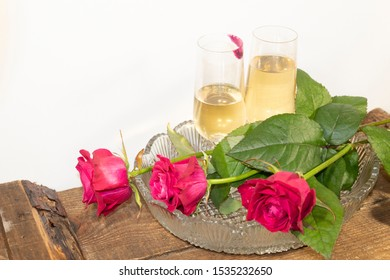 On a crystal platter, two glasses of wine. On one of the glasses is a trace of lipstick. In front are three red roses.
