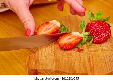On the cutting Board are several ripe juicy strawberries, one of them is cut by a steel knife in a woman's hands