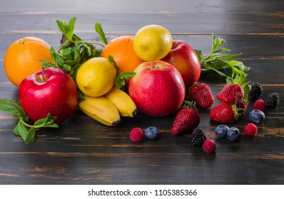 on dark background bananas, oranges, mint, berries. dietary food fresh fruit and berries on a wooden table. healthy products apples, citrus fruits, berries.