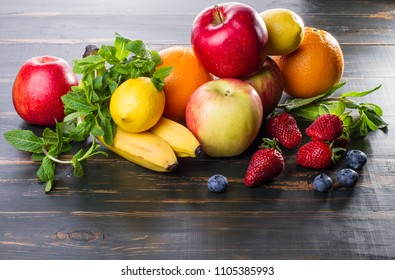 on dark background diet products. fresh fruit lie on a wooden table. healthy food apples, citrus fruits, berries.