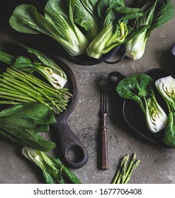 On a dark gray background, green asparagus and green cabbage Bok Choy.