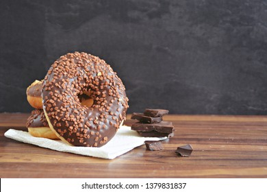 On a dark wooden surface with a black background donuts are stacked, one leaning against the pile. This is covered with chocolate pieces. Concept of delicious fresh donuts with chocolate beside it