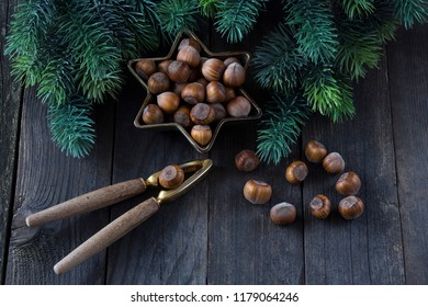 on a dark wooden table nuts in a bronze vase in the form of a star, an old nutcracker and pine branches around - winter background