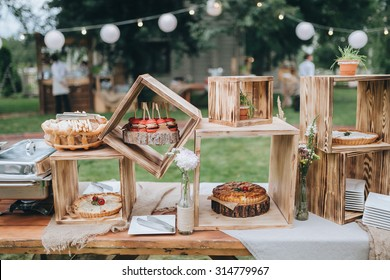 on decorated buffet table in wooden boxes are cakes and snacks