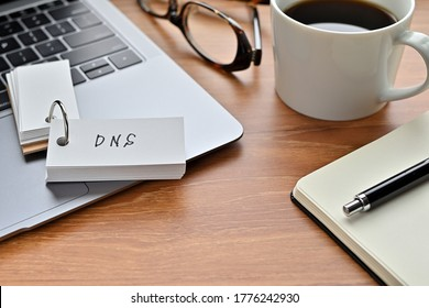 On a desk with a laptop, glasses, coffee, and a notebook, a vocabulary book was placed open There. The word DNS is there. It's an acronym that means Domain Name System.