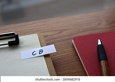 On the desk there is a clipboard, a notebook, and a stickynote with the word CB written on it. It was an abbreviation for the financial term convertible bond.