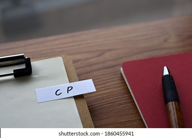 On the desk there is a clipboard, a notebook, and a stickynote with the word CP written on it. It was an abbreviation for the financial term commercial paper.