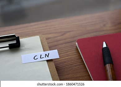 On the desk there is a clipboard, a notebook, and a stickynote with the word CLN written on it. It was an abbreviation for the financial term credit linked note.