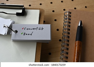 On the desk there is a notebook, a clipboard, and a word book with the word convertible bond.