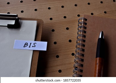 On the desk there is a notebook, and a stickynote with the word BIS written on it. It was an abbreviation for the financial term Bank for International Settlements.