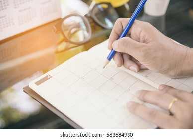 On diary and Calendar page,Female hand planner or organizer writing daily appointment.Woman mark and noted schedule(holiday trip) on book at office desk.Calendar reminder event for planner concept