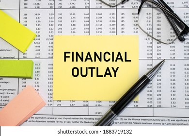 On the document with the numbers near the glasses and pen is a yellow sheet with the inscription financial outlay. Business and financial concept