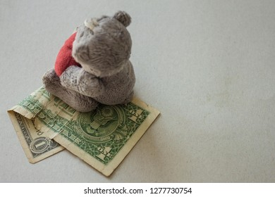 On a dollar bill is a toy bear cub, a children's toy. Expenses for the child, low state allowance, small compensation, paternal alimony. A toy of mass production.