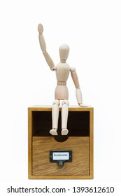 "On a drawer that says ""business,"" a special joint doll sits up and holds her hand. The background is white."