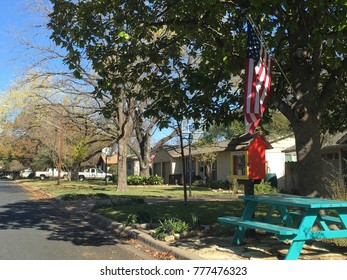 On the drive to work these are my streets of Austin , Texas USA On a nice sunny day bright green picnic table with American flag on the side of the street in community neighborhood Austin, Texas