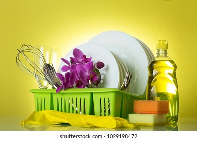 On drying rack clean dishes, utensils, glove, sponge and flowers Orchid on yellow
