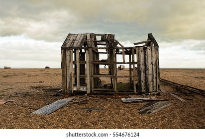 On Dungeness Beach, Kent, England, a derelict wooden hut on a shingle beach in the foreground, a derelict clinker-built fishing boat seen through holes in the hut, under cloudy storm skies