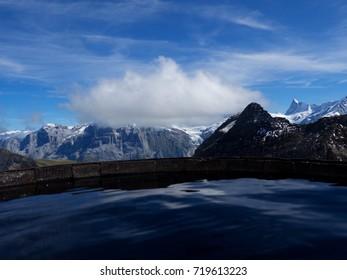 On the Edge of Basin for the Rain Water at Faulhorn Peak in Switzerland with Blue Sky and Big White Cloud - oberland, schweiz, swiss, switzerland, bern, luzern, zurich, canton, zermatt, cervino, tirol