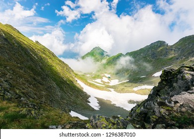 on the edge of rocky cliff of Fagaras valley. gorgeous landscape of Romanian mountains in rising clouds. popular travel destination. beautiful summer scenery with snow on the bottom of the valley