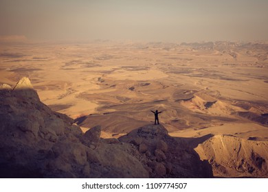 On the edge of a rocky cliff a man raises his hands to heaven as a sign of freedom or victory with a fantastic landscape at the background. Concept of: breathing, freedom, journey, life, love.
