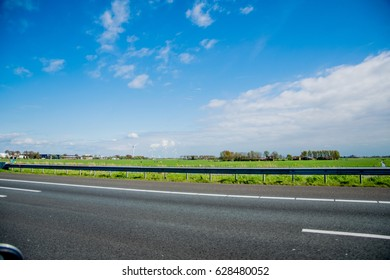 on a european road with green grass and blue sky