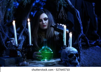 On eve of Halloween witch casts a spell, uttering a terrible curse on bottles of potion.Fabulous, spooky voodoo shack.Magic Shine.Fabulous and mystical concept.Fashionable toning.Creative color.