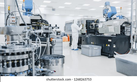 On a Factory Scientist in Sterile Protective Clothing Work on a Modern Industrial 3D Printing Machinery. Pharmaceutical, Biotechnological and Semiconductor Manufacturing Process Shot from Inside.