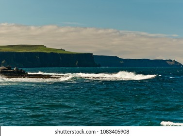 On a ferry passing Crab Island, Galway Bay, looking southeast toward the Cliffs of Moher, O'Brien's Tower along ridge, up and left of center.  Doolin Harbor, County Claire, Ireland.