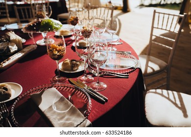 On the festive table in the wedding banquet area there are candles, plates, glasses, lie cutlery and napkins