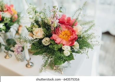 On the festive table in the wedding banquet area there are compositions of flowers and greenery, next are the candles
