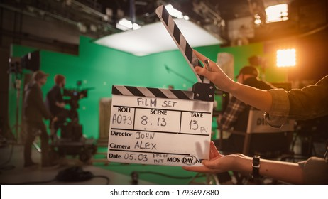 On Film Studio Set Camera Assistant Holds Clapperboard. Green Screen Scene with Talented Cameraman in the Background. Close-up Shot.