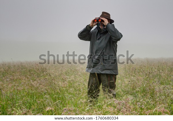 On a foggy, rainy day, a hunter stands in the high meadow and watches with his binoculars whether young deer are in the meadow.
