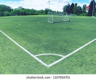 On football field. Behind goal of soccer field. Soccer football net background over green grass or soccer field and blurry stadium and soccer players.