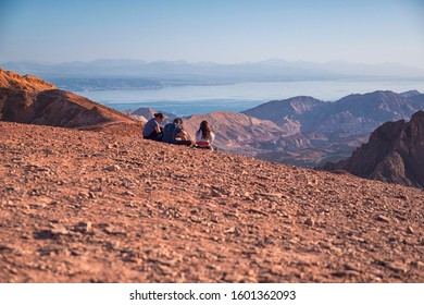 On foreground hikers sitting on a cliff and enjoying the view over Eilat valley with the city and the red sea on the backgound hill slit by the sunset