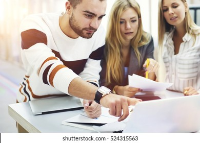 On frontage, professional media coach pointing mistakes in students pres-release published on web page while on blurred background two young female pupils listening explanation making notes with pen