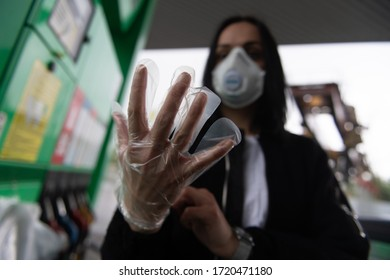 On a gasoline station woman is wearing protective gloves.