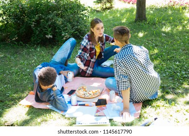 On the grass. Modern stylish students feeling rested and relieved while sitting on the grass while having picnic